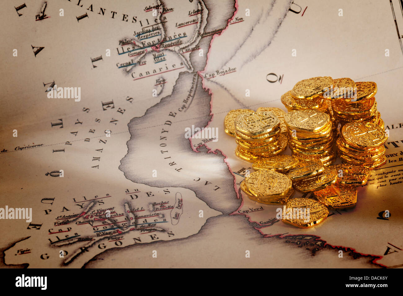 Doubloons and Treasure Map - Old map of Atlantis and a pile of gold doubloons. - Stock Image