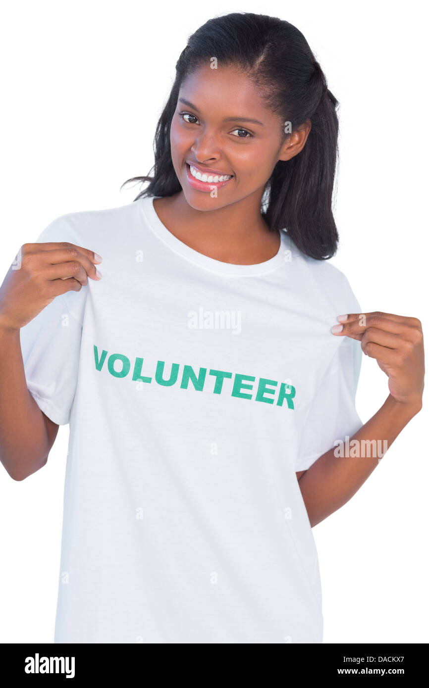 Young woman wearing volunteer tshirt and pointing to it - Stock Image