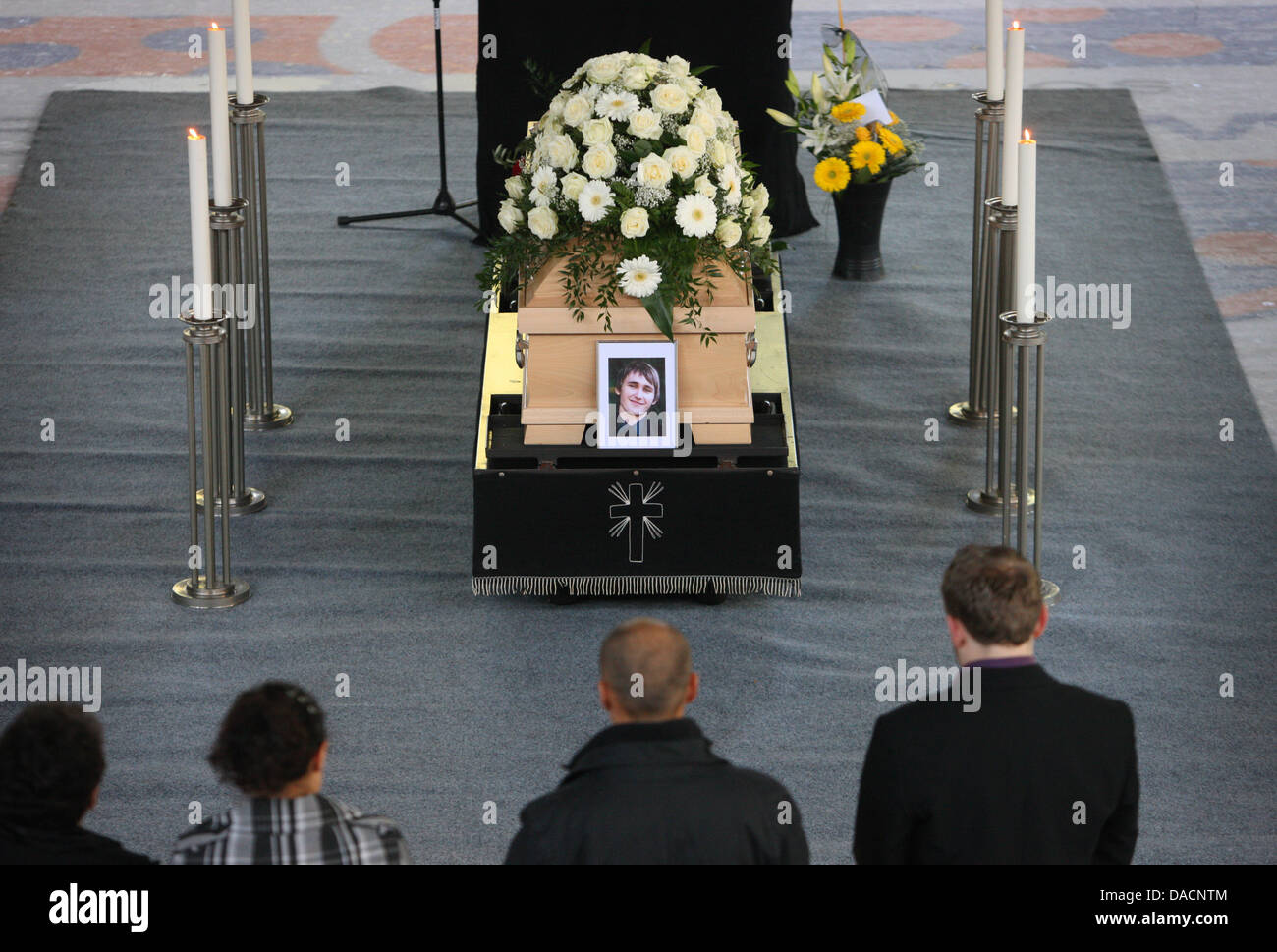 Friends and relatives of RobertDietrich stand at his coffin during his funeral at the Ice Stadium in Kaubeuren, - Stock Image