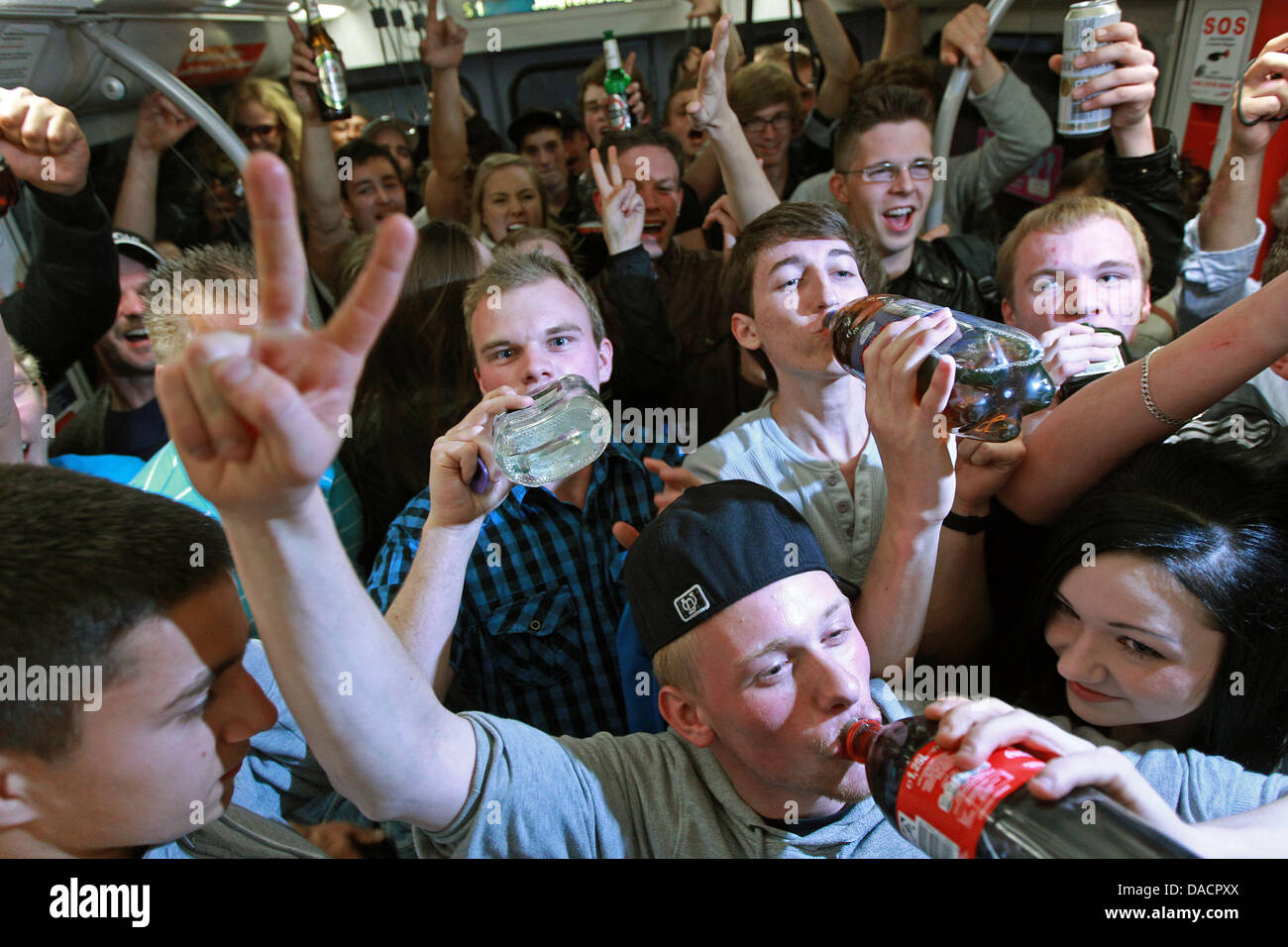 Adolescent celebrate during the so-called 'HVV farewell drinking' in the underground in Hamburg, germany, - Stock Image