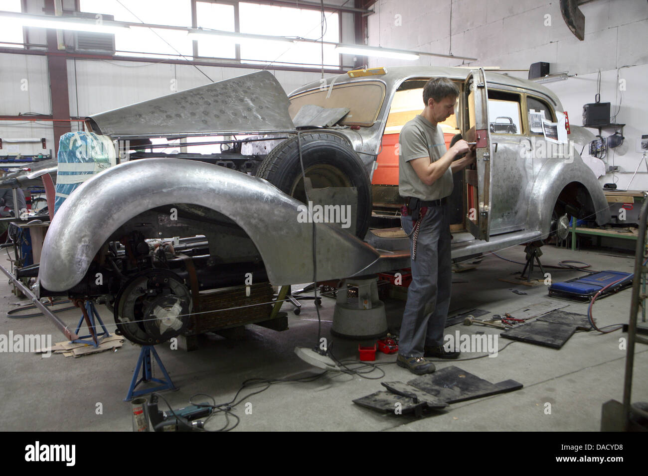 Automobile mechanic Peter Spillner works on the car body of a Mercedes-Benz 770 from 1941 in his workshop in Glienick, Stock Photo