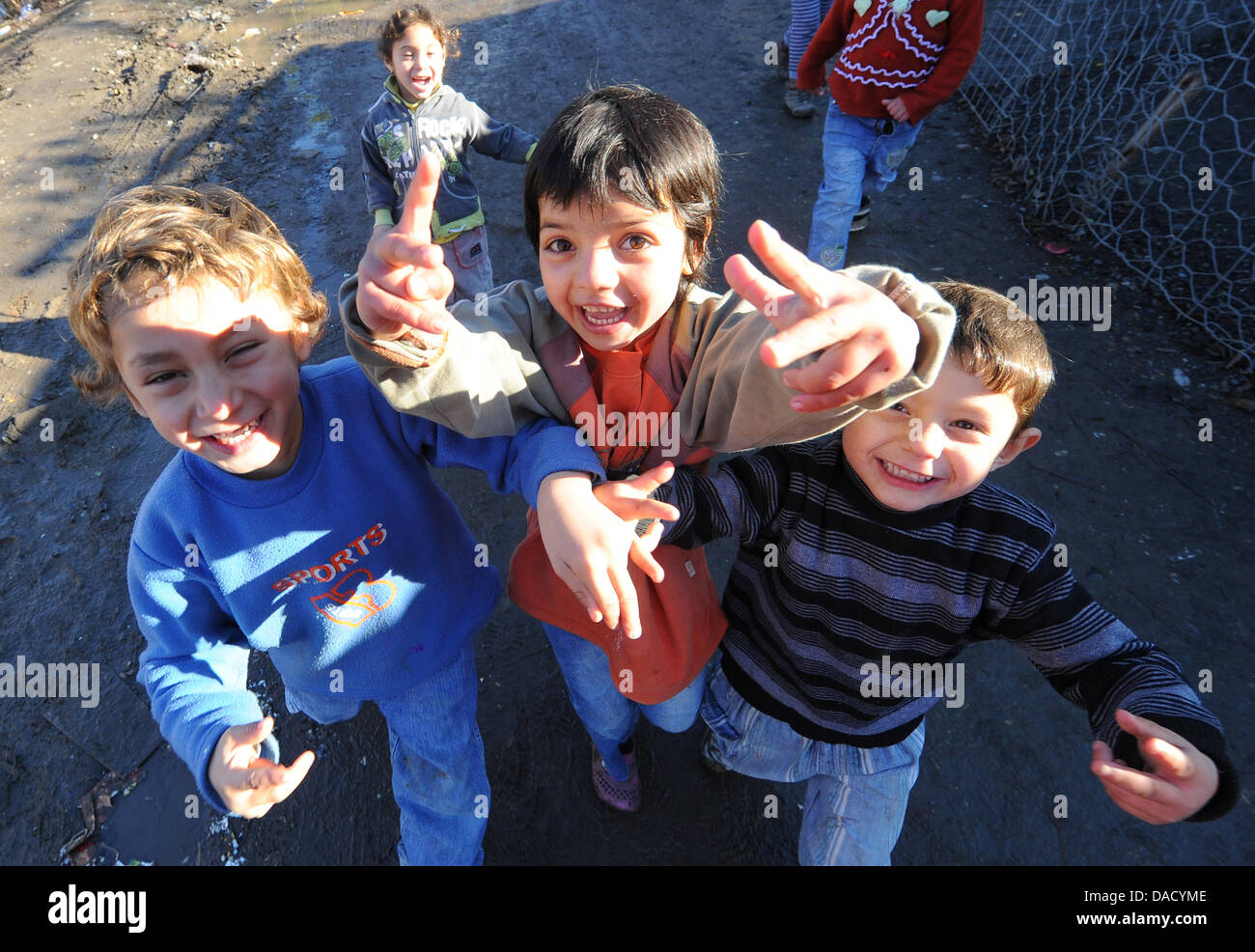 Roma children laugh and look into the camera at the refugee