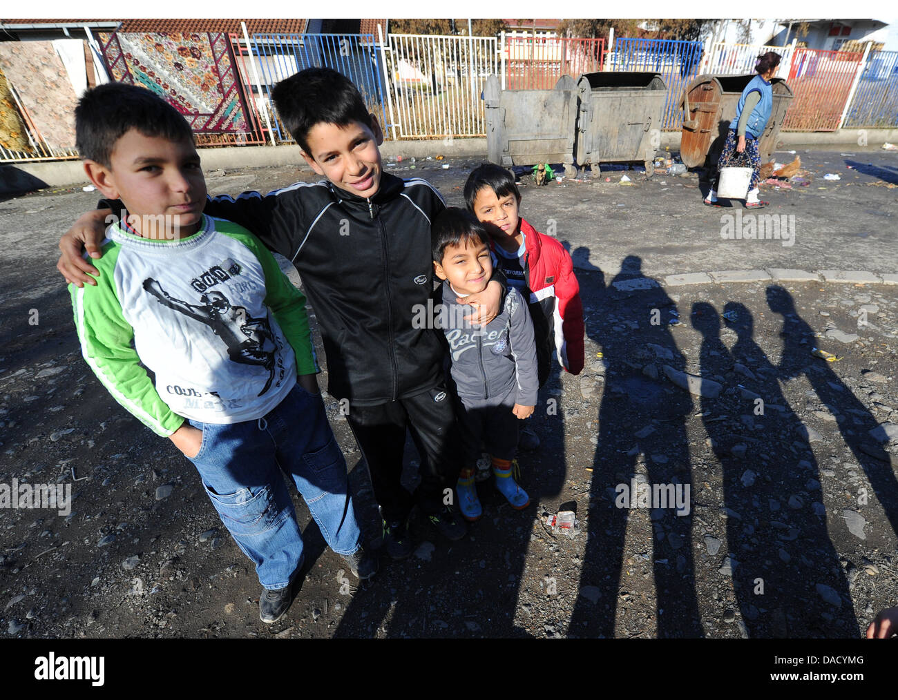 Roma children pose for the camera at the refugee camp in