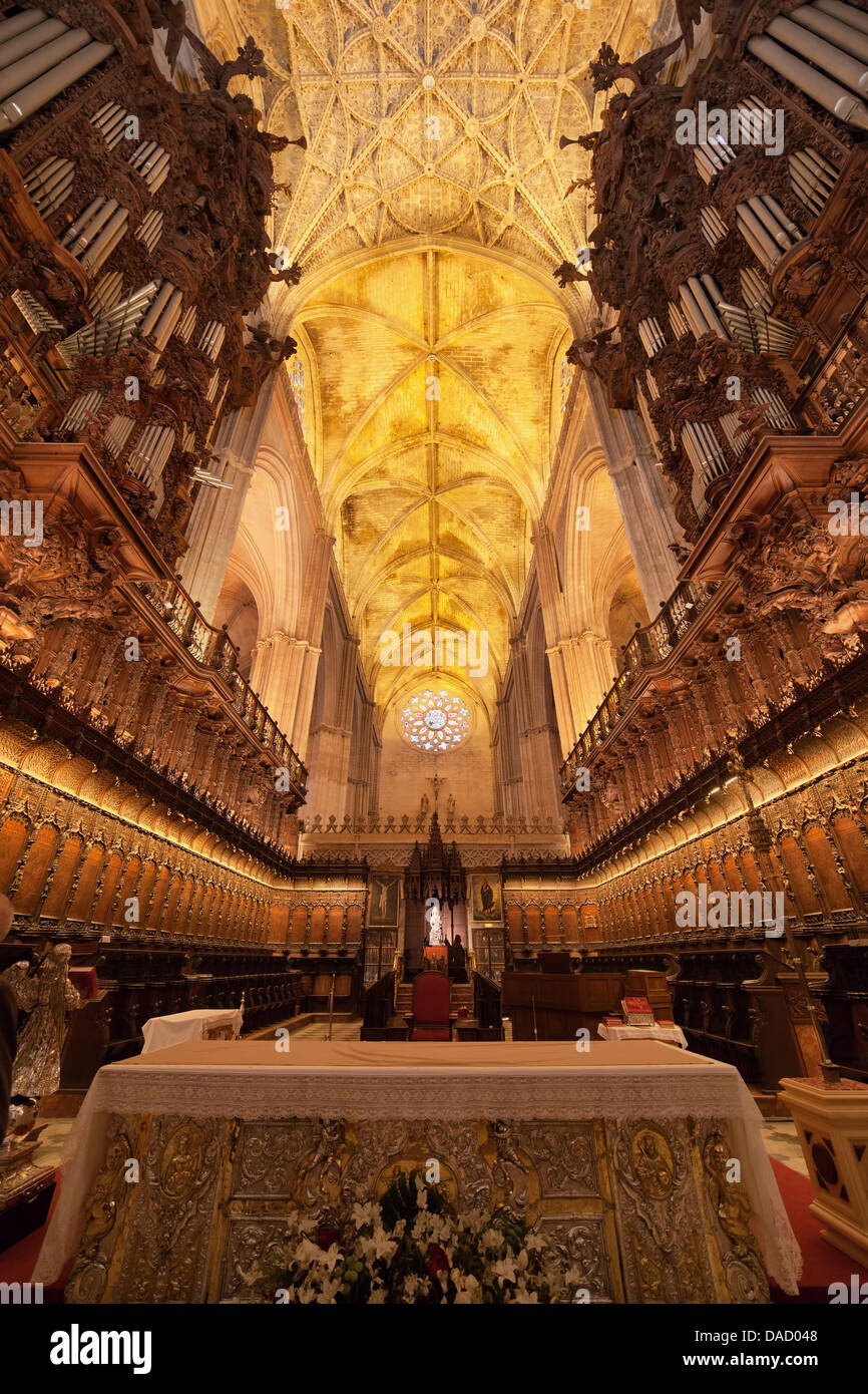 Interior of the Seville Cathedral, pipe organ, choir stalls, Gothic vault in Spain, Andalusia region. - Stock Image