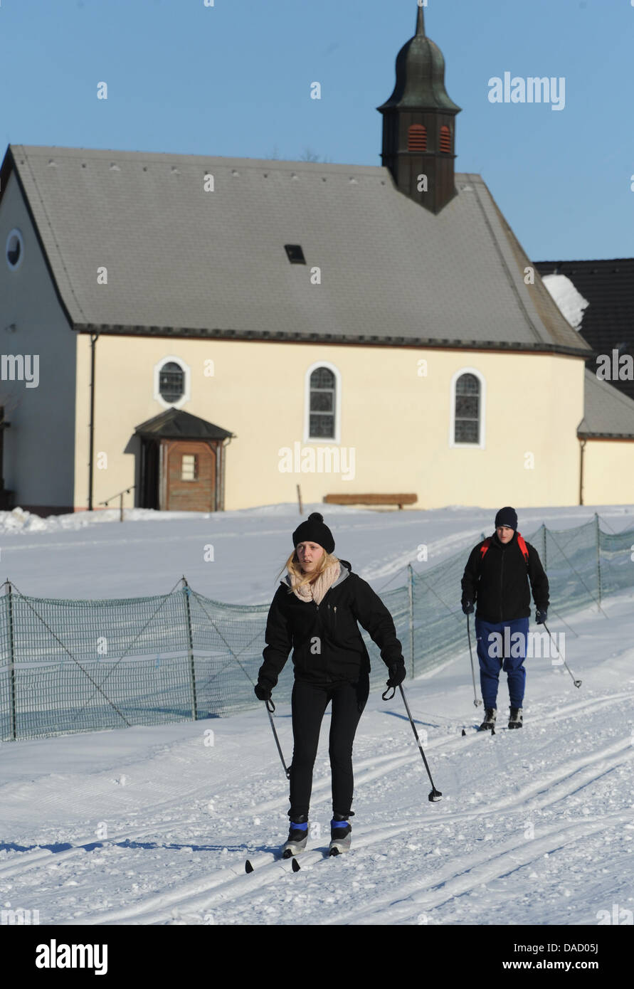 Two cross-country skiers go past the chapel at the skiing trail at the Thurner mountain near St. Maergen, Germany, - Stock Image