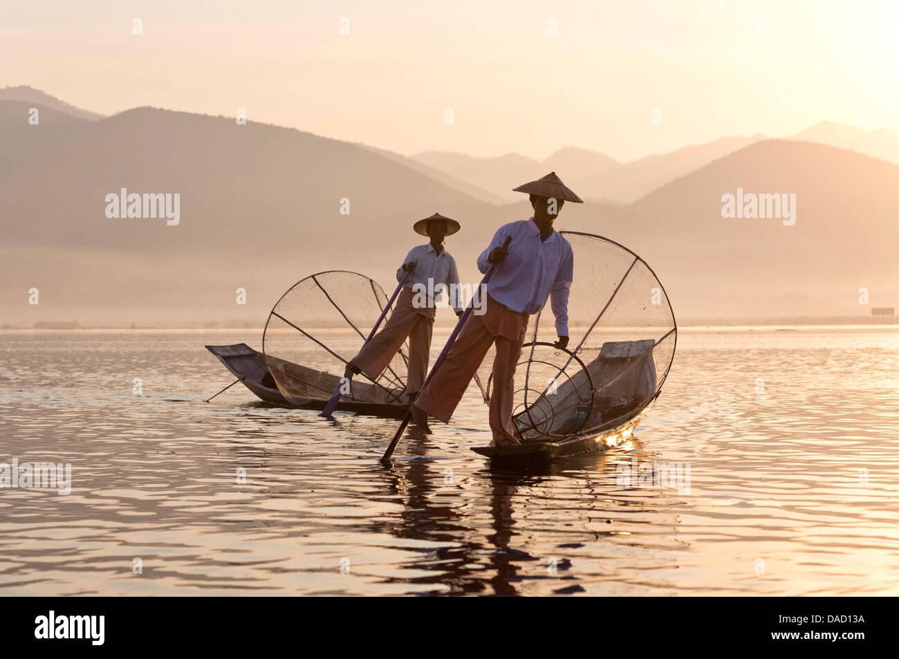 Intha 'leg rowing' fishermen at sunset on Inle Lake, Inle Lake, Myanmar - Stock Image