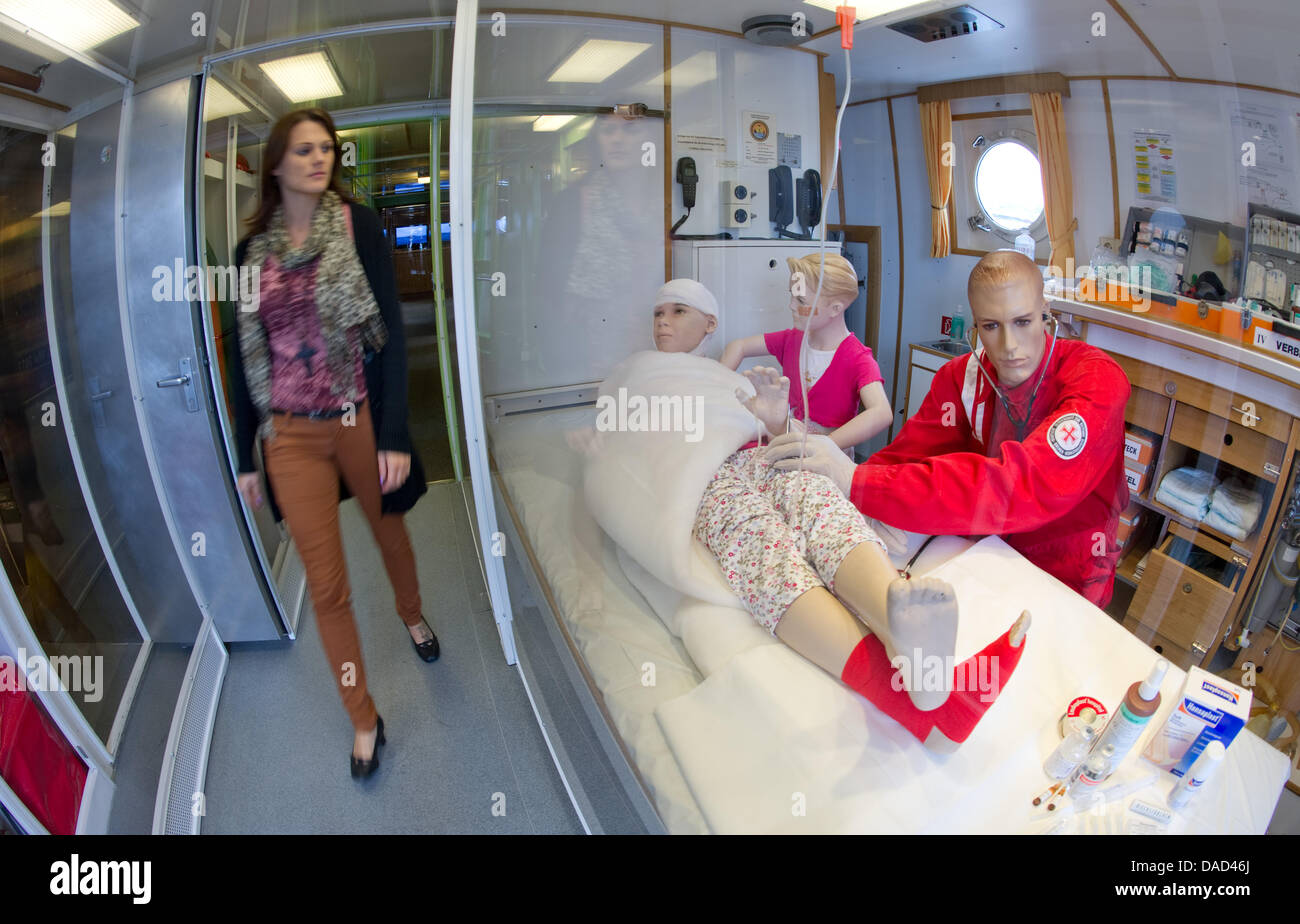 A woman observes a mock medical treatment held at the rescue cruiser 'John T- Essberger', which is exhibited - Stock Image