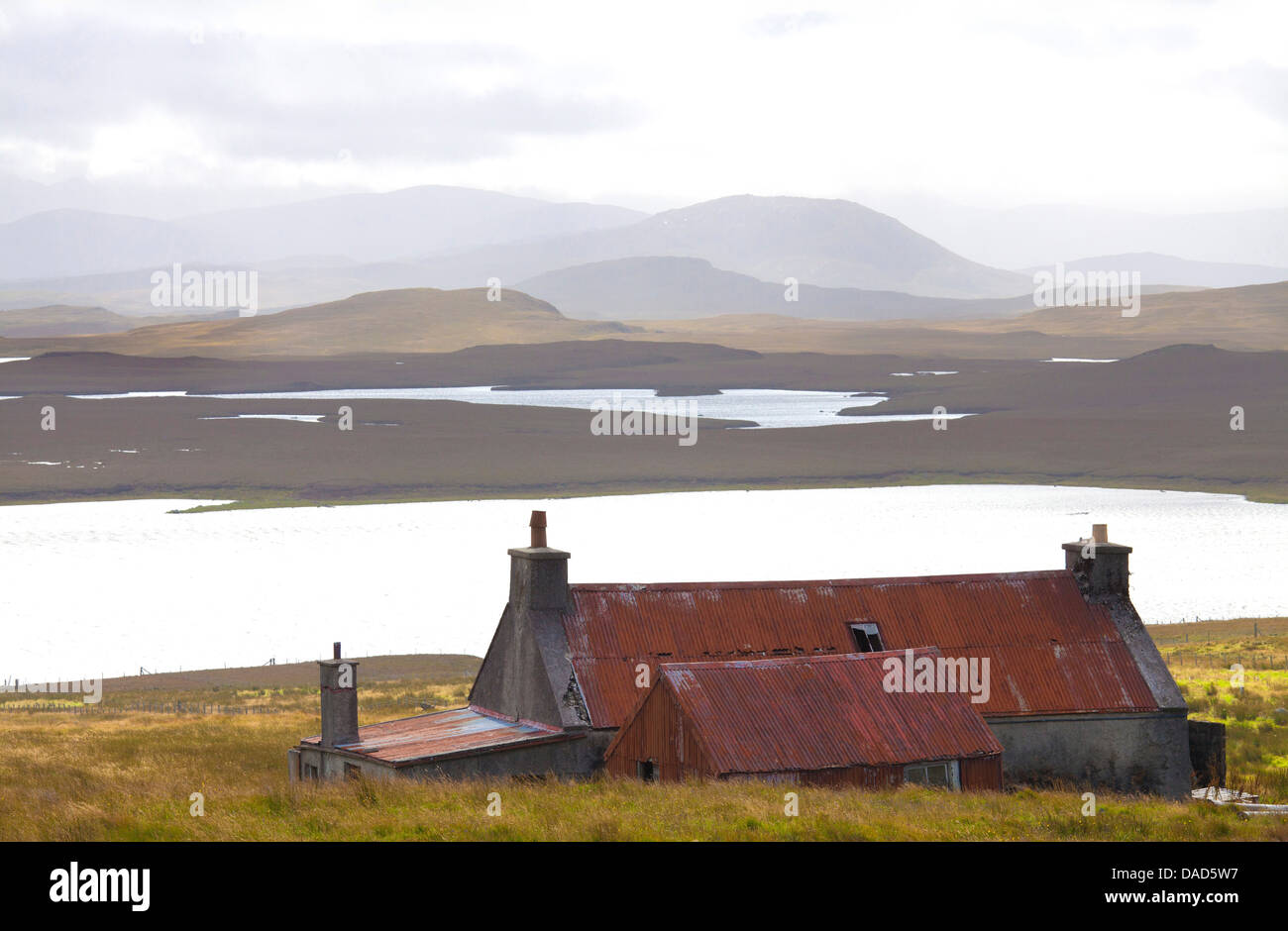 Farmhouse with red iron roof overlooking lochs and mountains off the A858 south of Carloway, Isle of Lewis, Scotland, - Stock Image