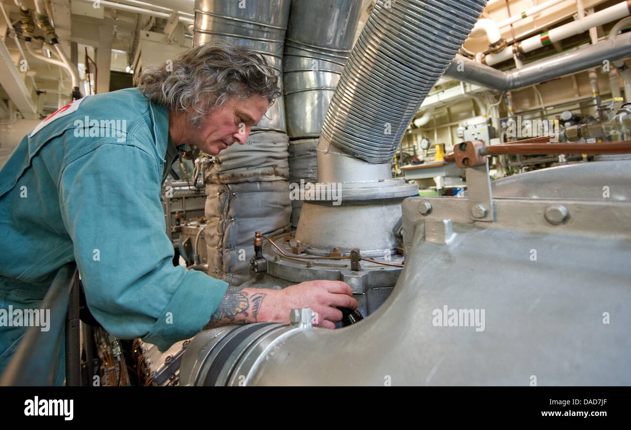 A crew member stands inside the engine room  of the rescue vessel 'John T. Essberger' at the Museum of Technology - Stock Image