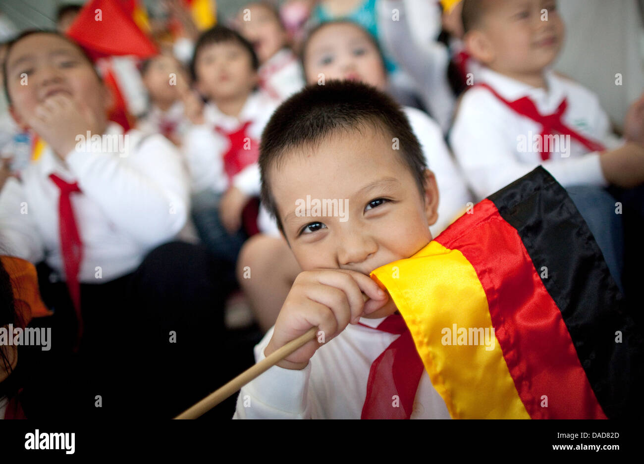 A Vietnamese boy holds a German flag Tourist guide while German Chancellor Angela Merkel attends the opening of - Stock Image