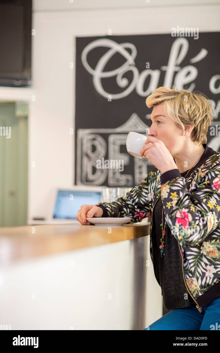 Woman drinking coffee at cafe counter - Stock Image
