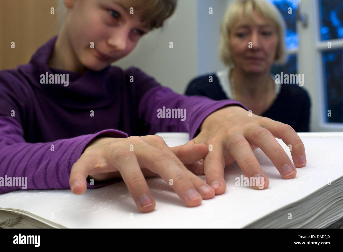 12 year old Anne reads the braille in her math book at the State ...