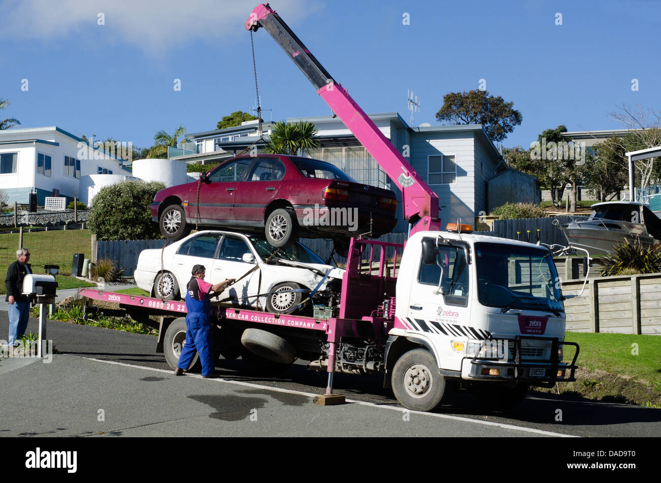 Man towing damaged car over a tow truck Stock Photo