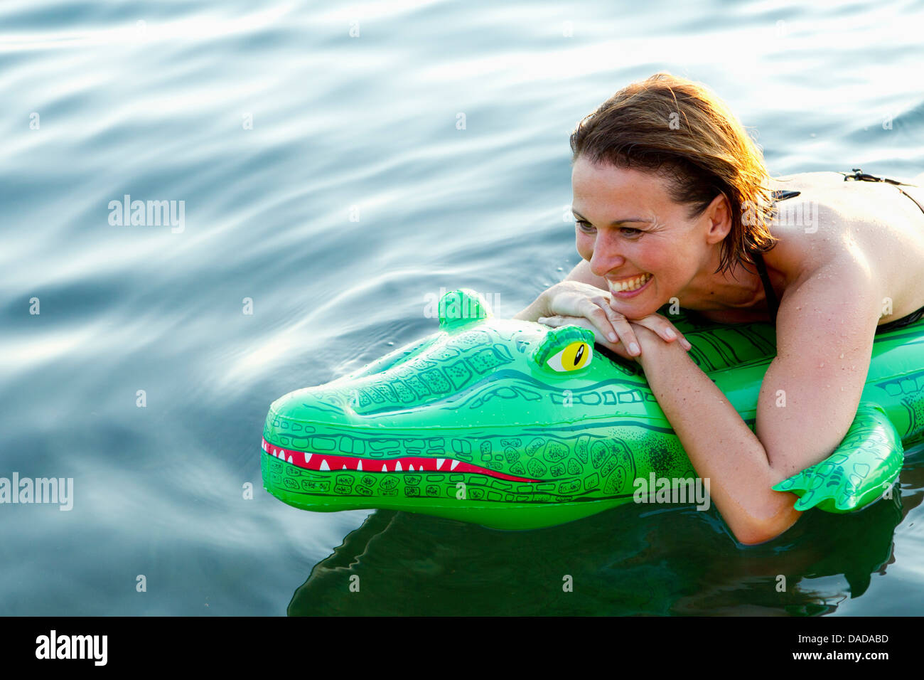 Woman in sea with inflatable crocodile - Stock Image