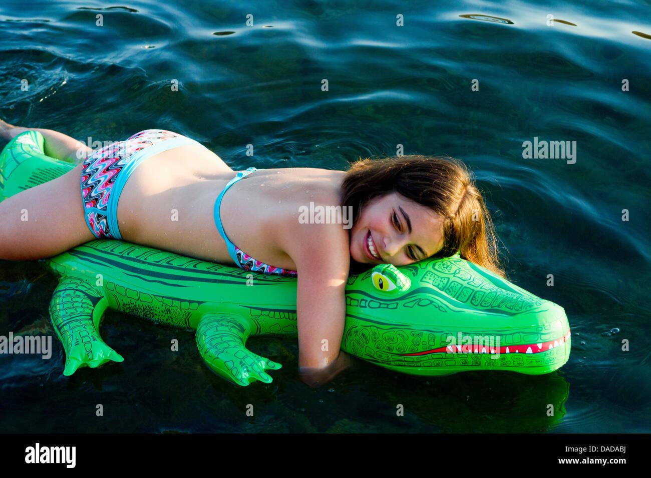 Girl in sea with inflatable crocodile - Stock Image