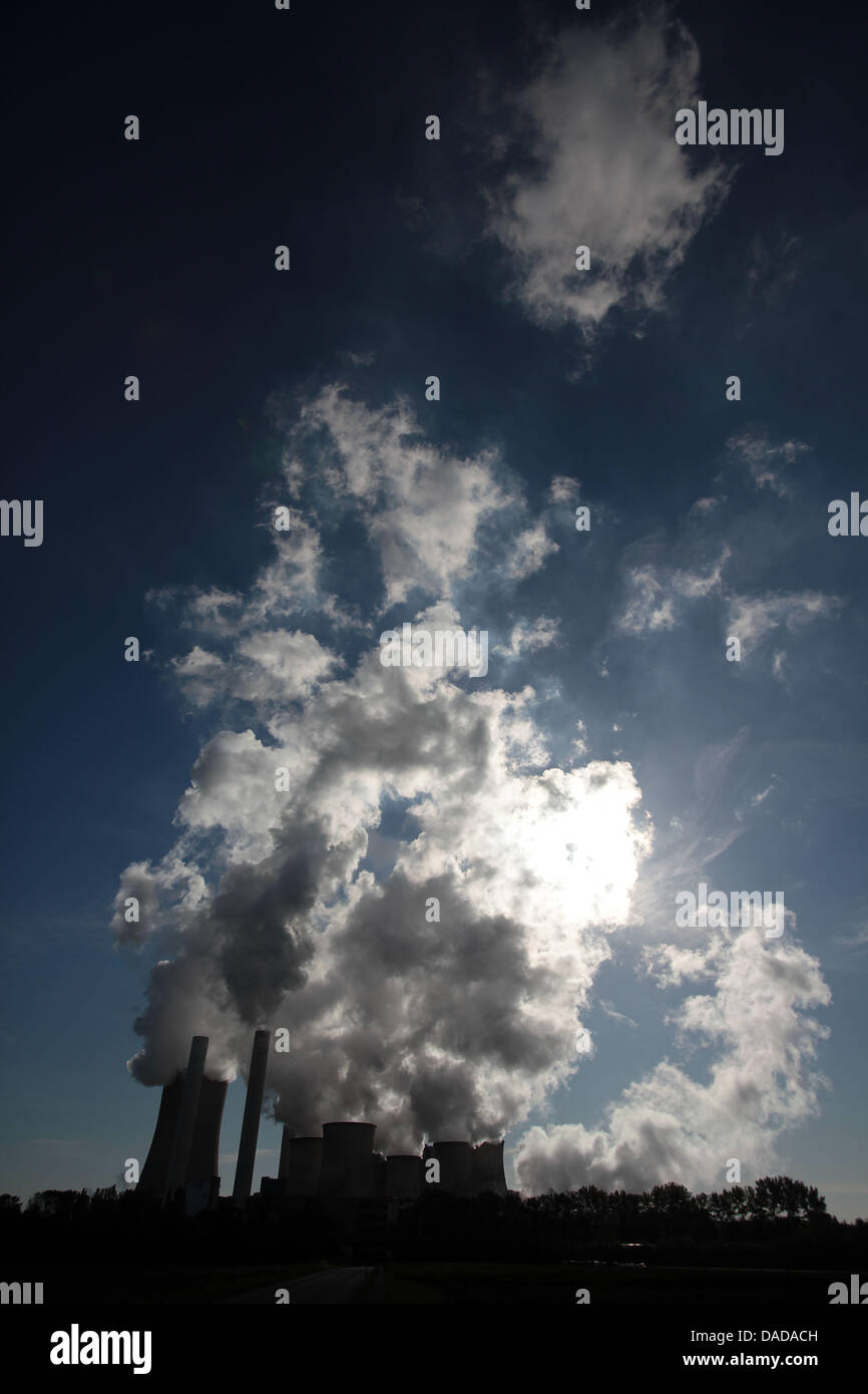 Smoke and water vapor rise from the cooling towers and chimneys of the Niederaussem brown coal power station owned Stock Photo