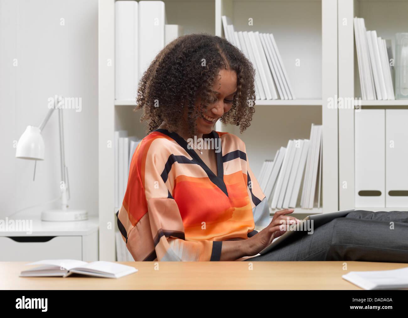 Smiling businesswoman using digital tablet - Stock Image