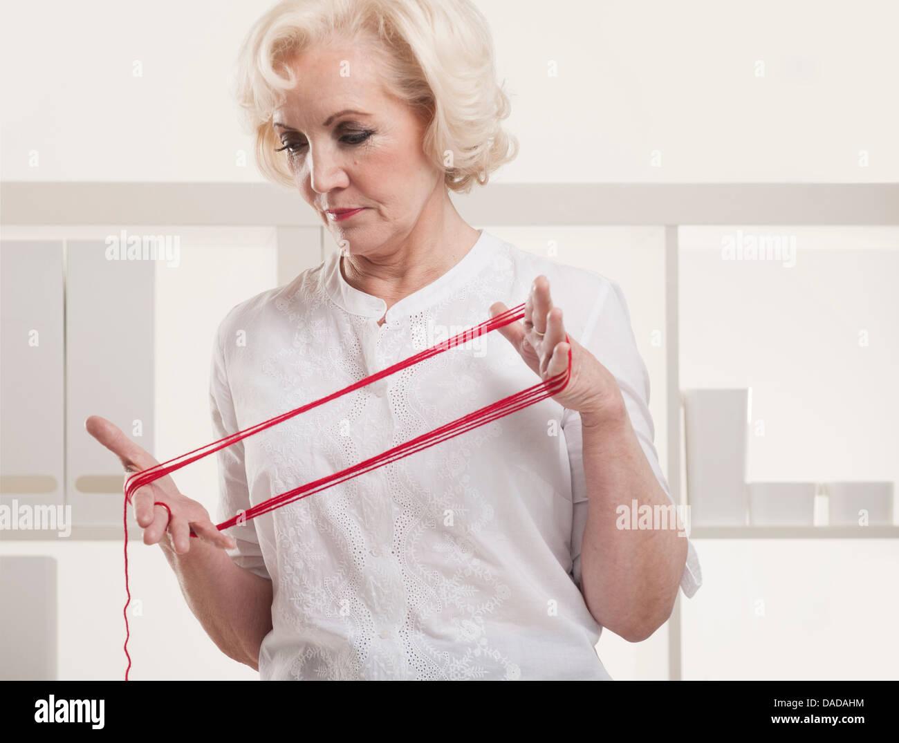 Senior woman winding yarn - Stock Image