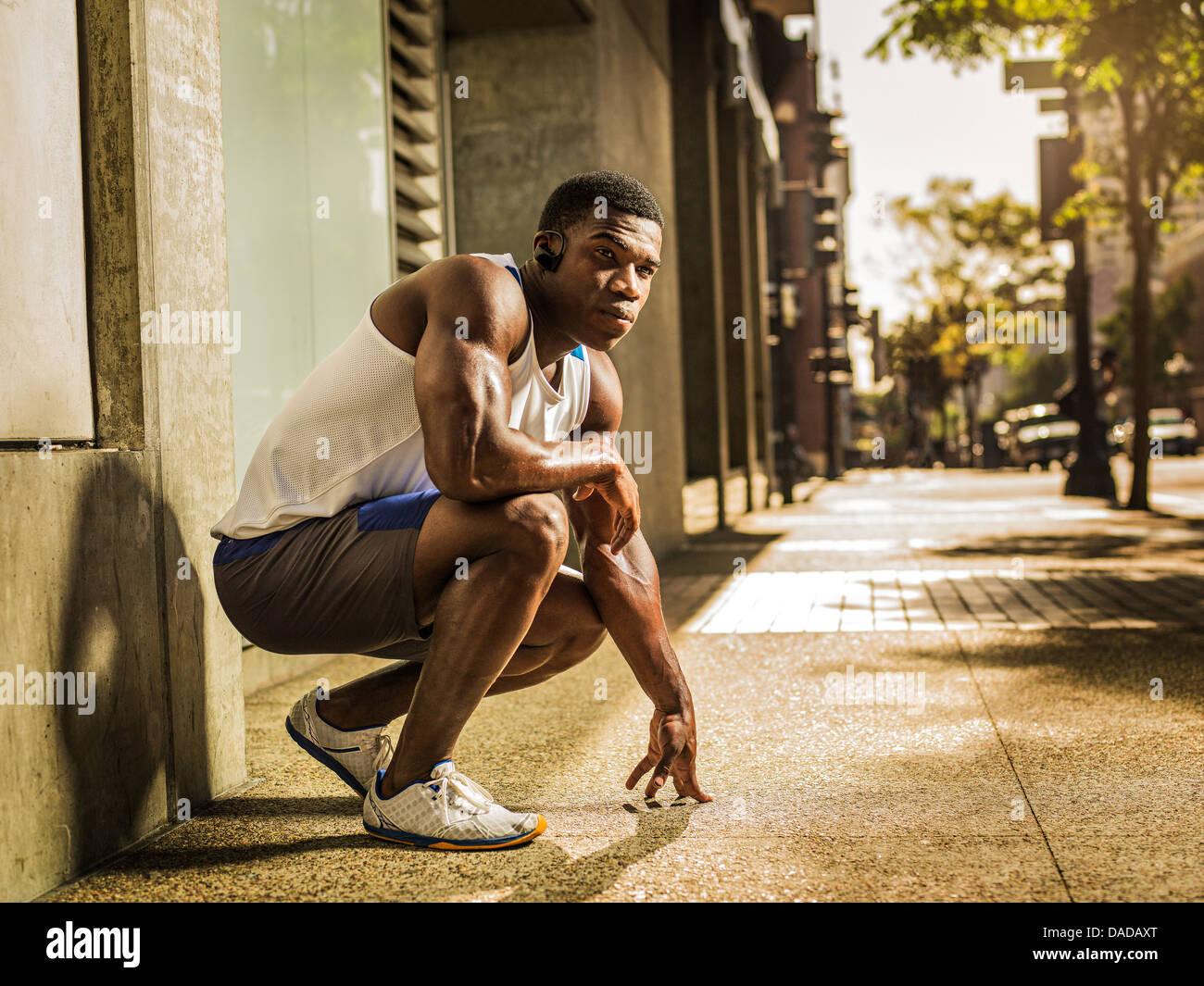 Runner crouching on street - Stock Image