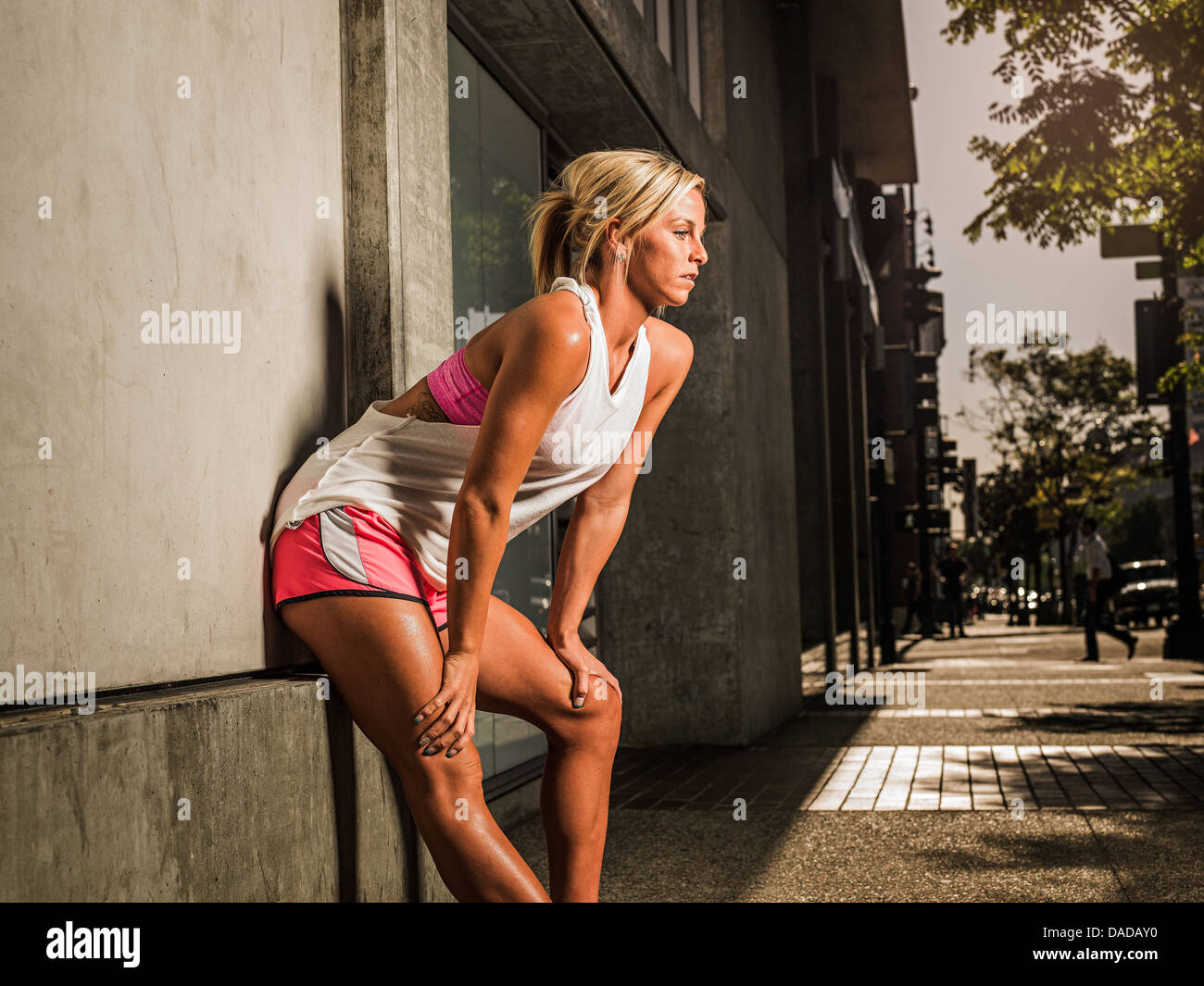 Female runner stopping to catch her breath - Stock Image