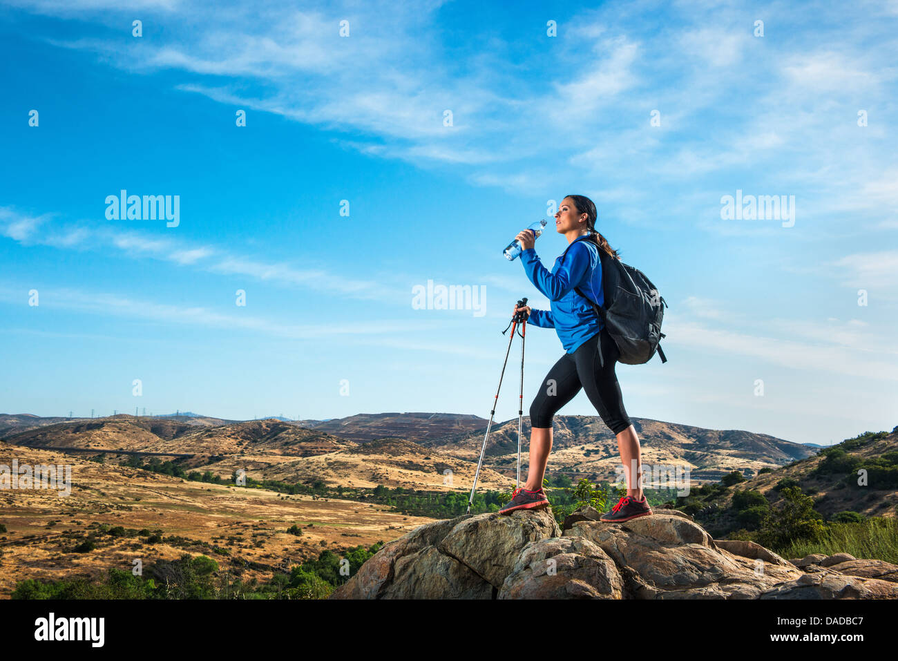 Female hiker on rock, drinking water - Stock Image