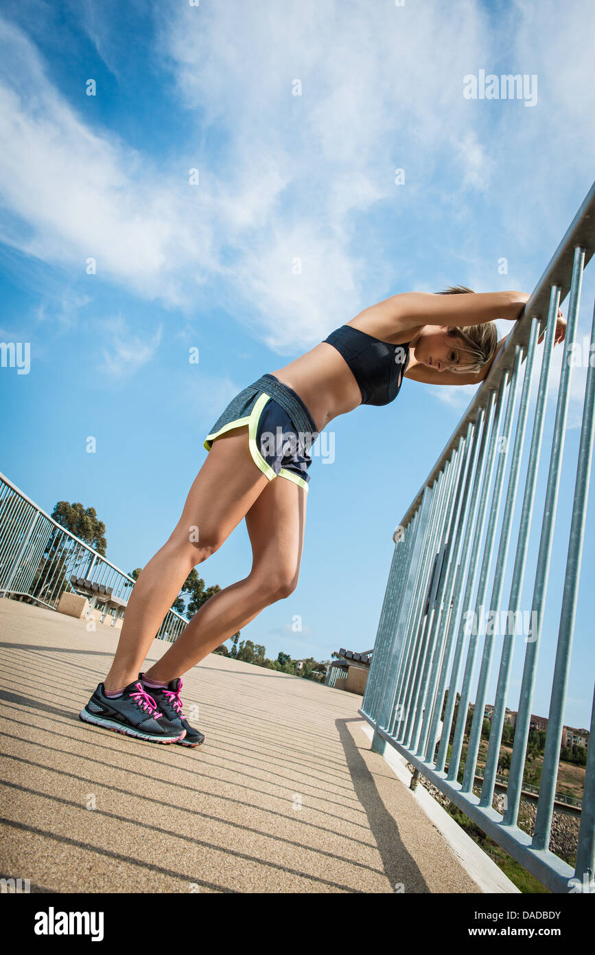 Female runner leaning on railing - Stock Image