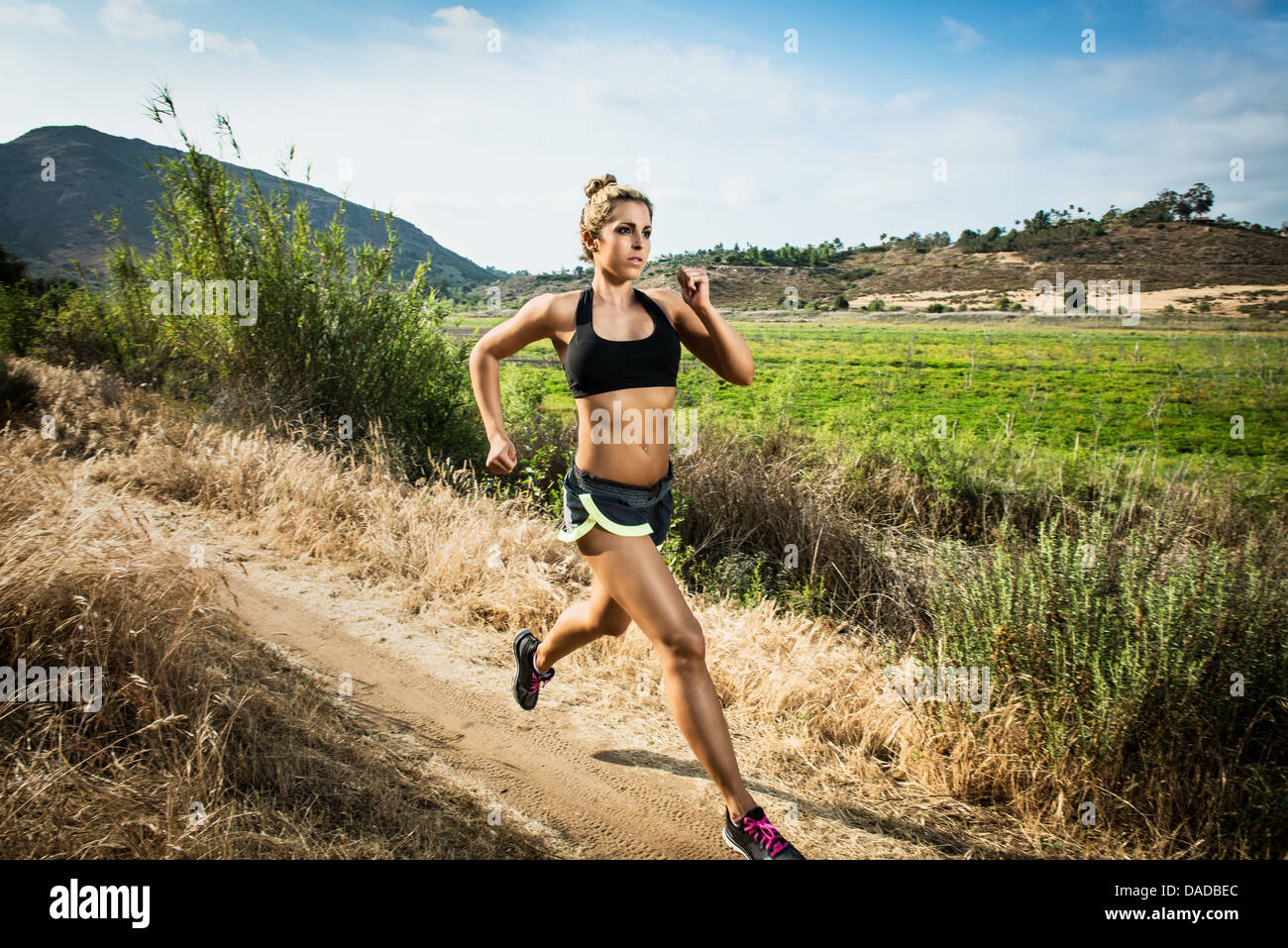 Female runner in rural landscape - Stock Image
