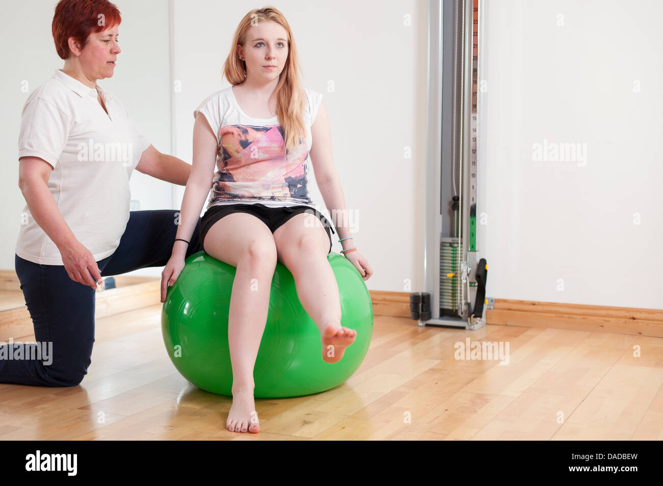 Young woman sitting on fitness ball, being guided by mature woman - Stock Image