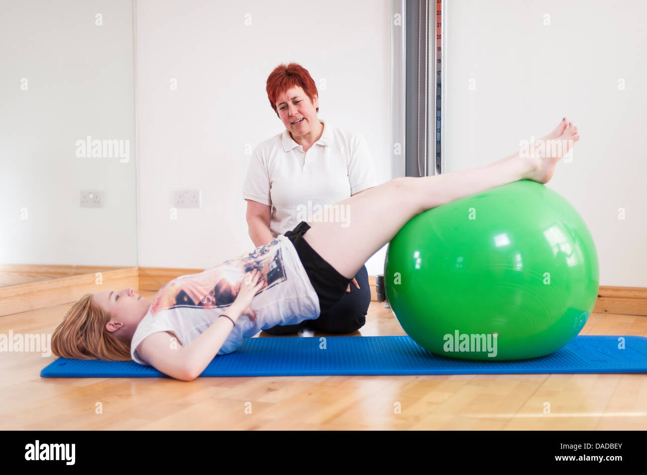 Young woman exercising with fitness ball, guided by mature woman - Stock Image