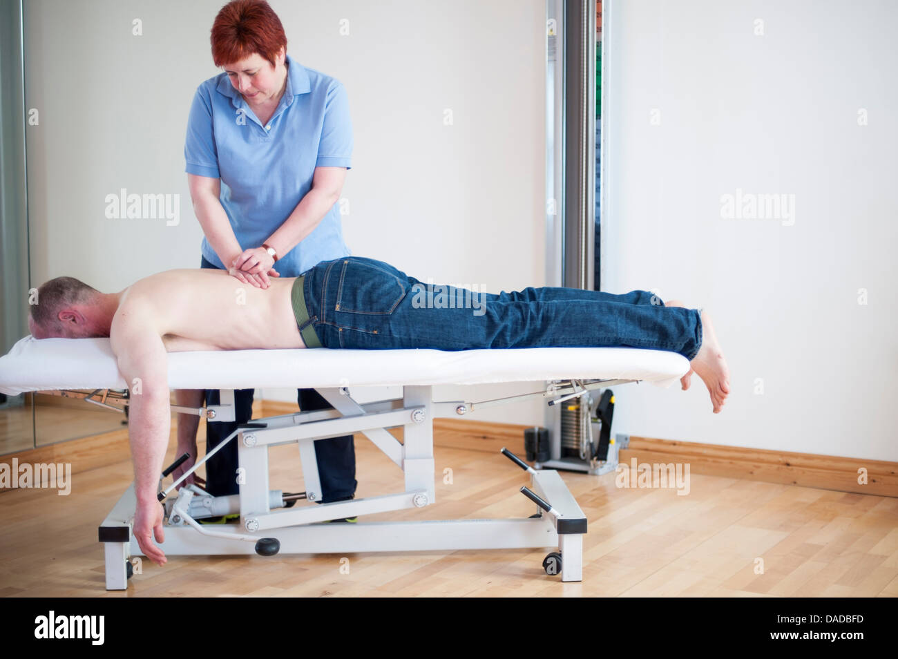 Man lying on front on massage table getting message - Stock Image