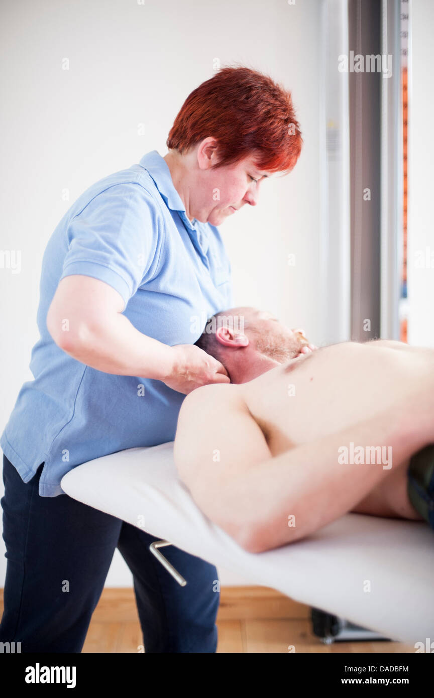 Man lying on back receiving head massage - Stock Image