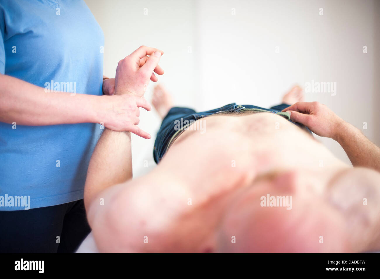 Woman checking man's pulse - Stock Image