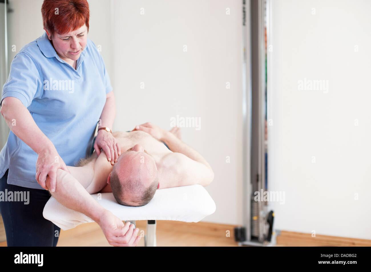 Woman giving man massage treatment Stock Photo