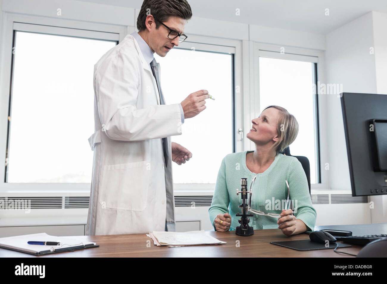 Man wearing lab coat holding test tube speaking to woman sat at desk - Stock Image