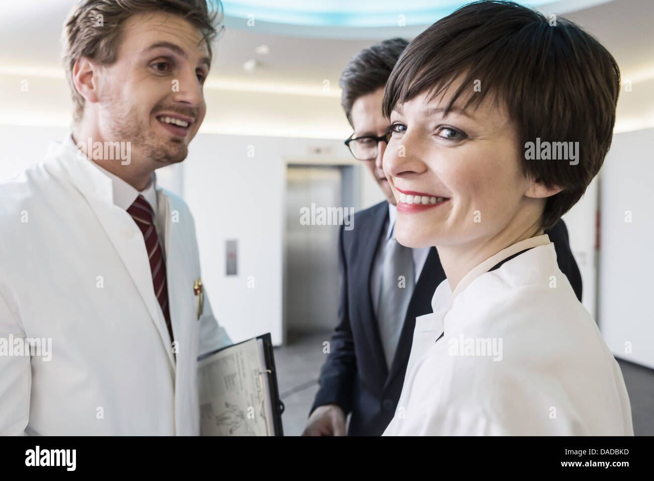 Three mid adults smiling in lobby - Stock Image