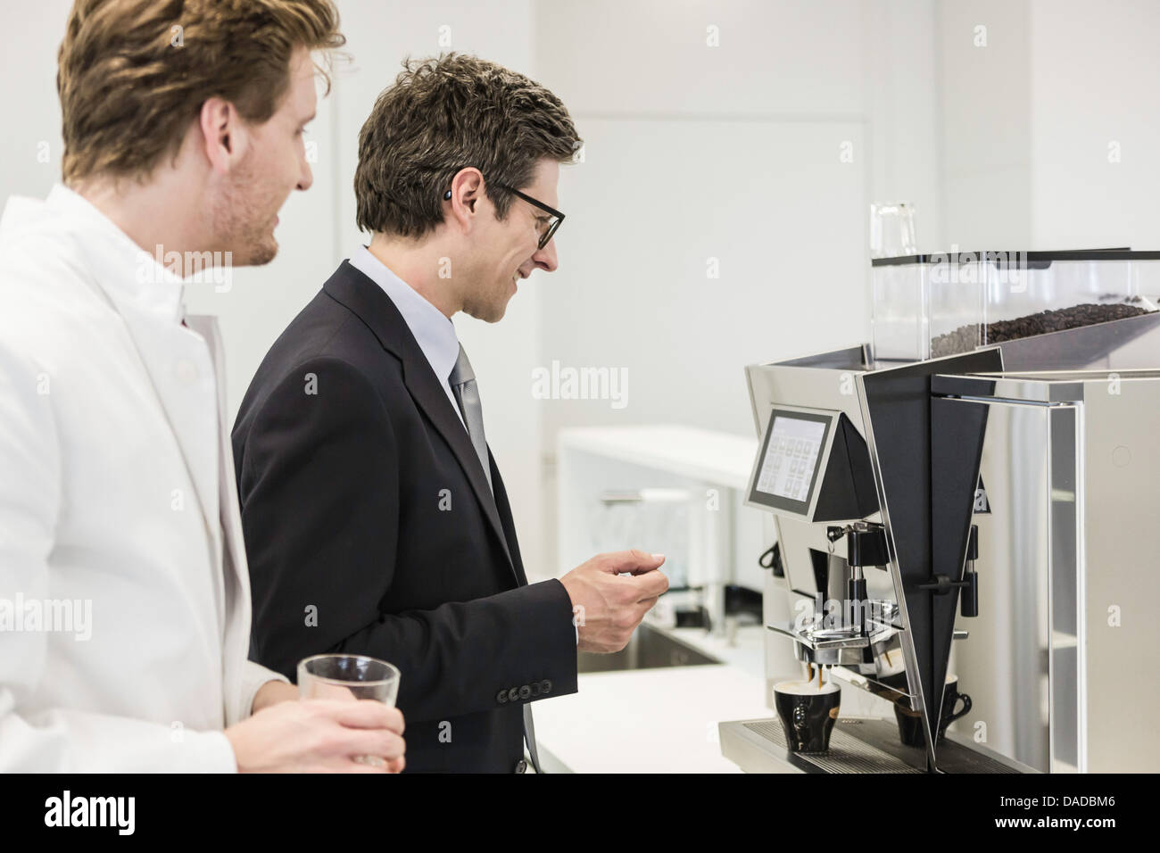 Man wearing business attire getting drink from coffee machine - Stock Image