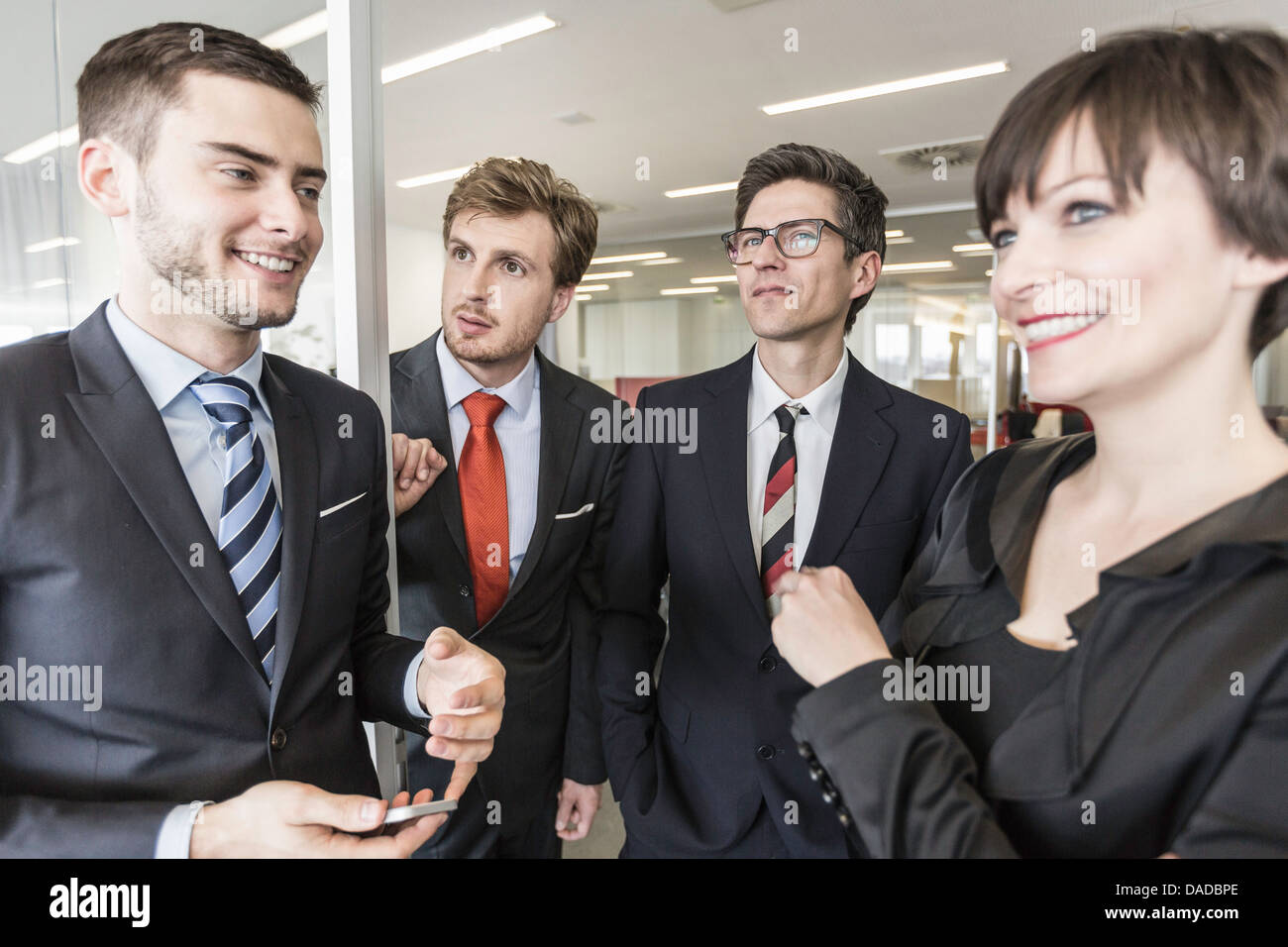 Businesspeople standing in office - Stock Image