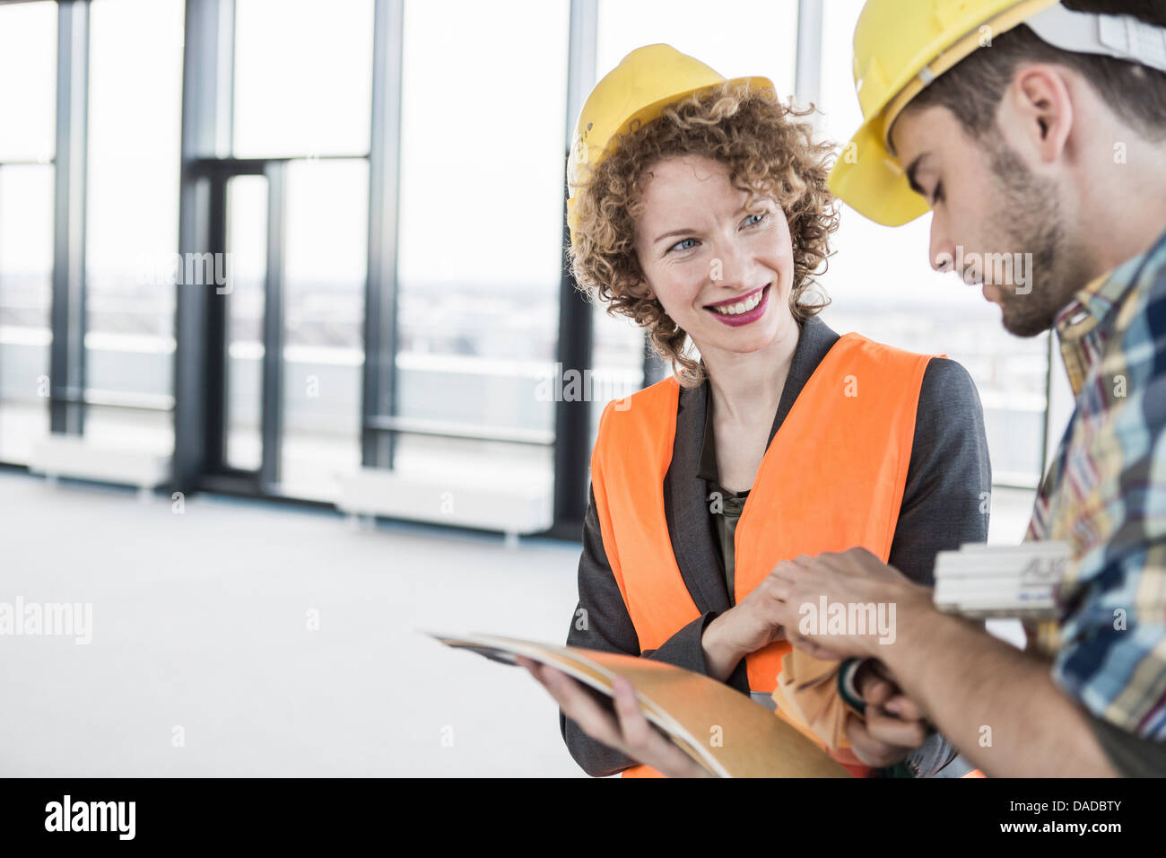 Builders wearing hard hats discussing project - Stock Image