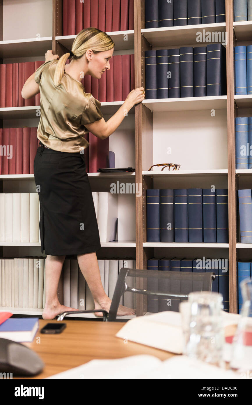 Female lawyer choosing books from bookcase - Stock Image