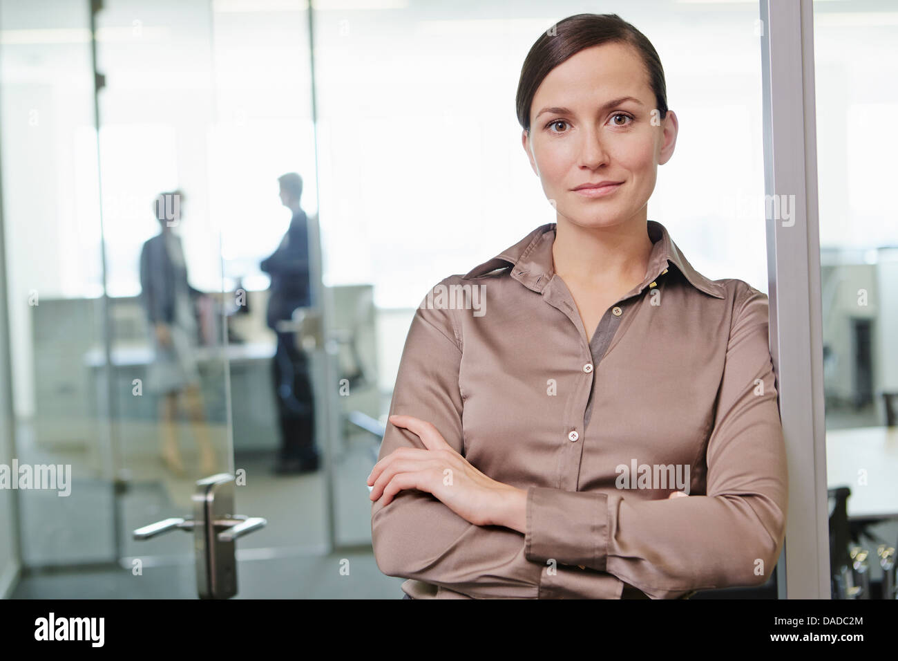 Mid adult woman standing in office with arms crossed - Stock Image