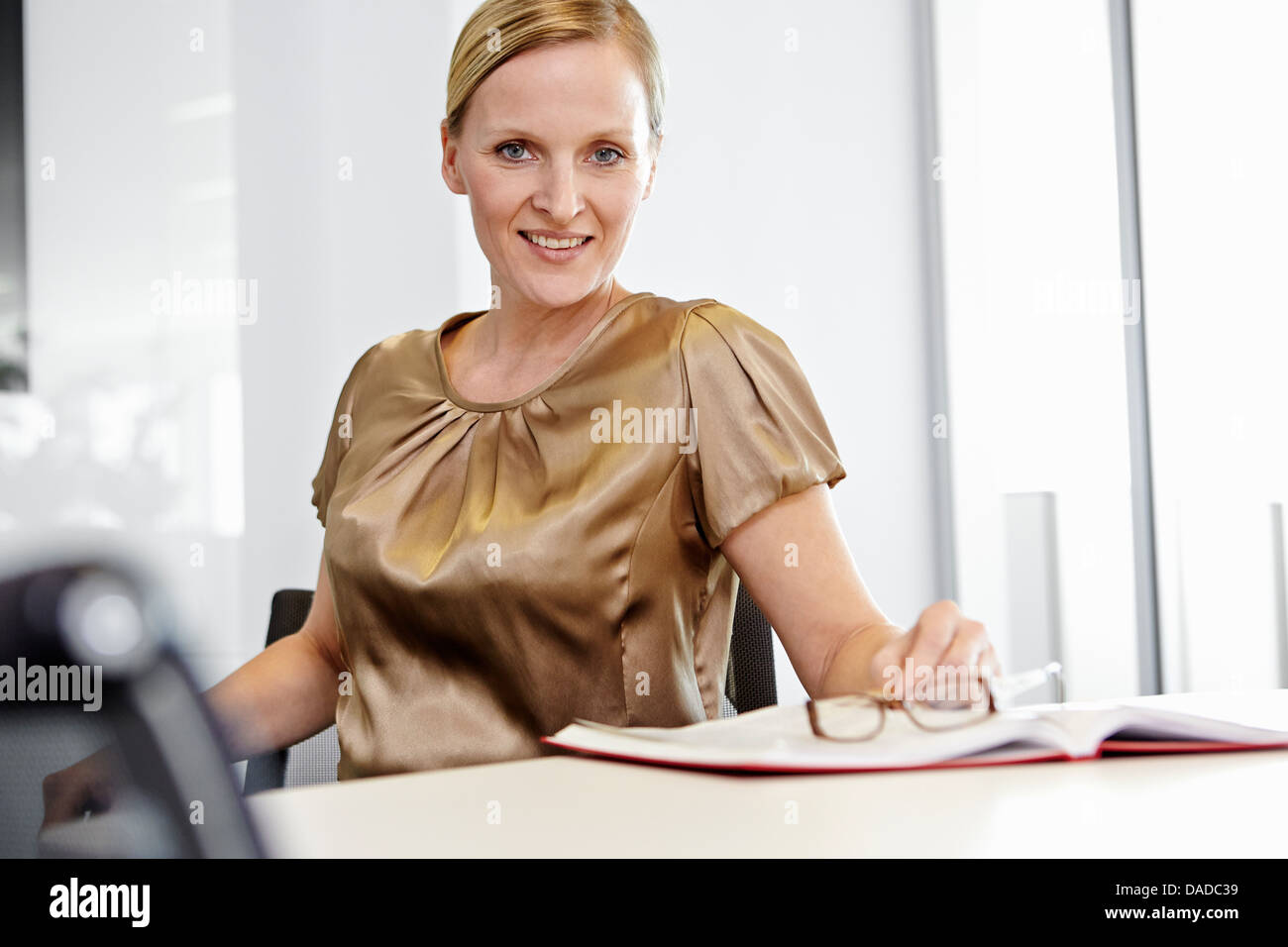 Business woman sitting on office chair, smiling - Stock Image