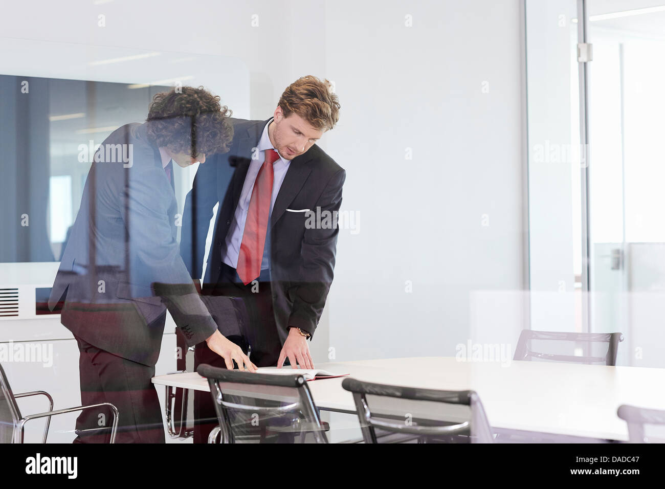 Businessmen Standing At Conference Room Table Looking At Paperwork - Standing conference room table