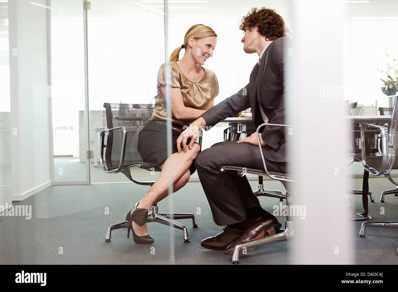 Businessman and woman having meeting at conference table - Stock Image