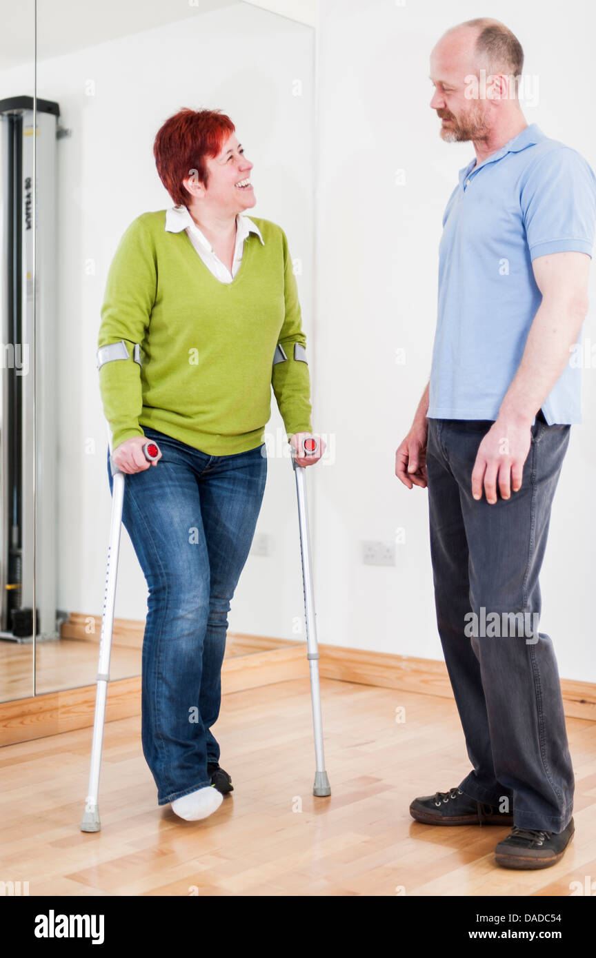 Woman using crutches talking to man - Stock Image