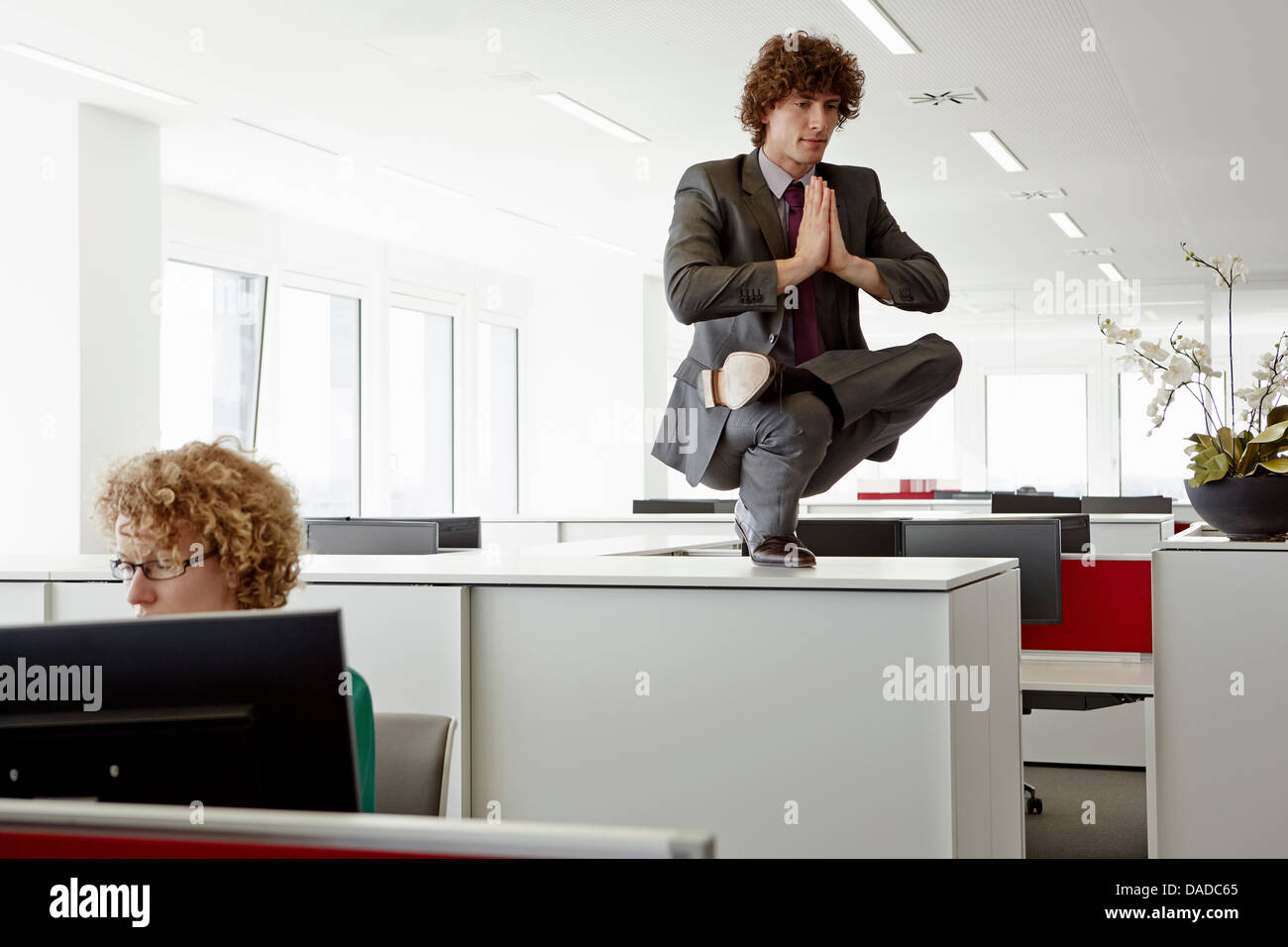 Businessman doing yoga pose on top of filing cabinet, behind woman working at desk - Stock Image
