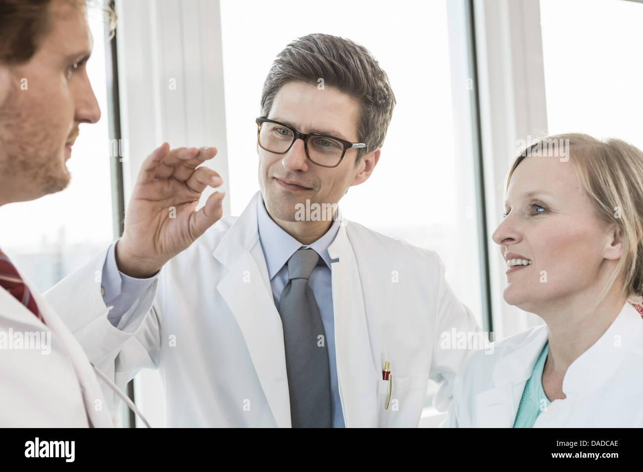 Three people wearing lab coats looking at medicine tablet - Stock Image