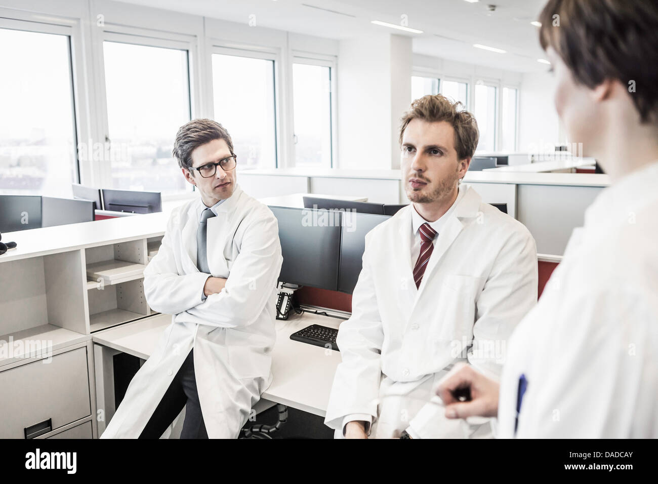 Two men wearing lab coats sitting on desk, woman standing - Stock Image