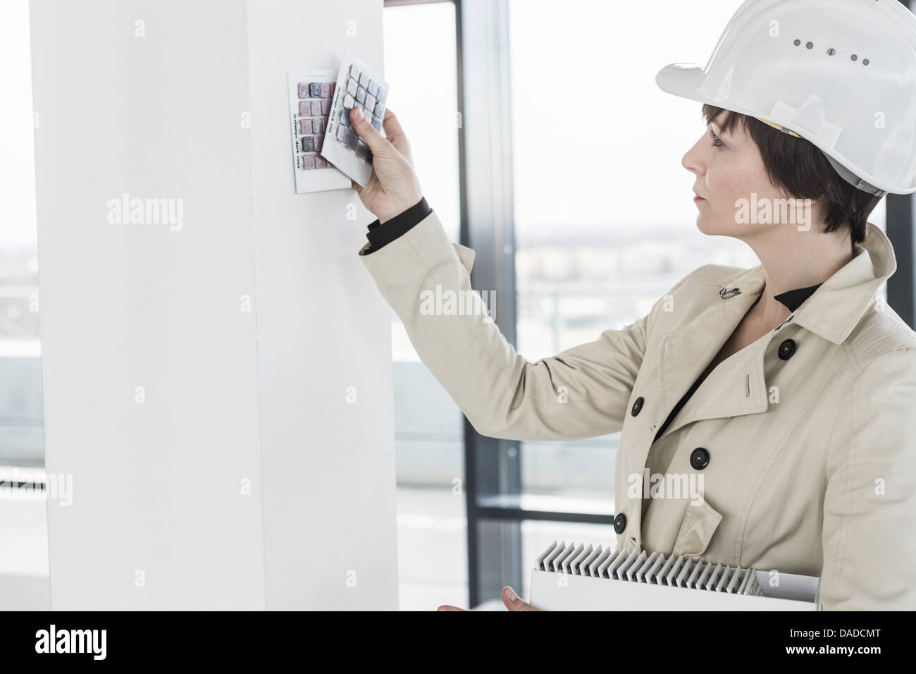 Female architect choosing wall colour samples - Stock Image