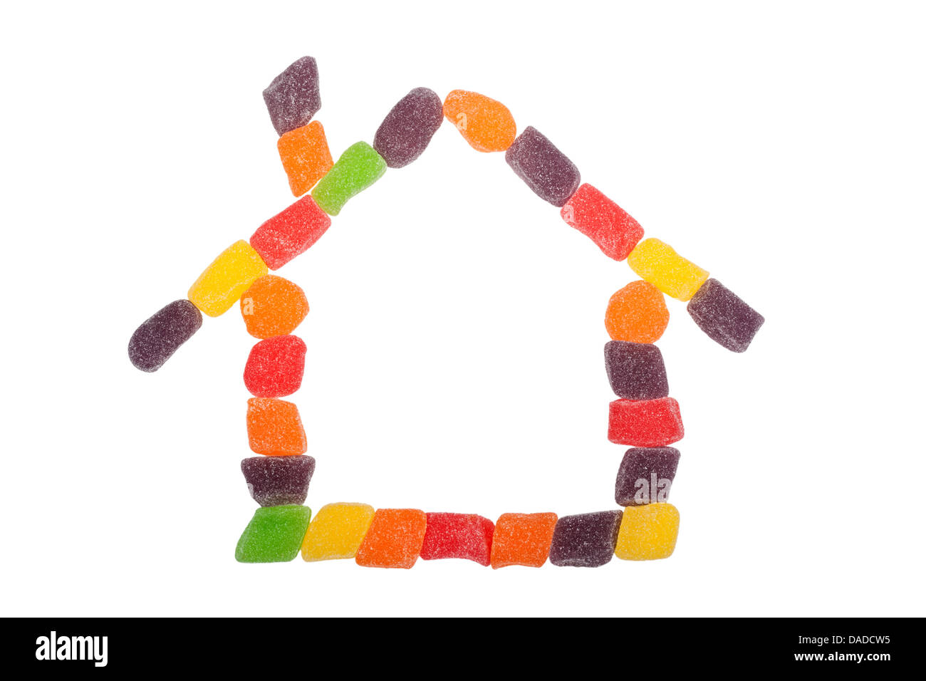 Pieces of candy forming the shape of a house isolated on white background - Stock Image