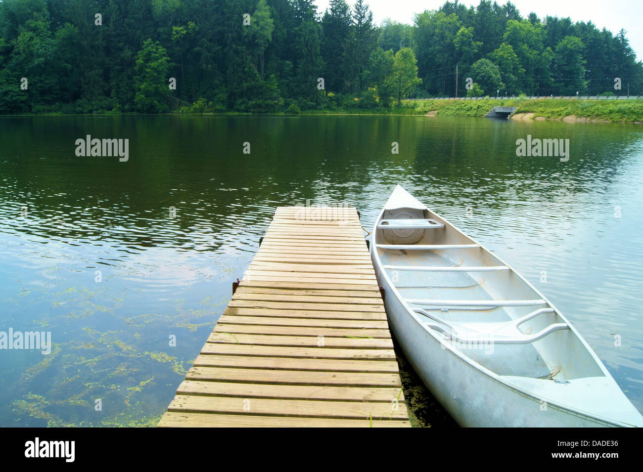 Silver canoe docked at a lake. Picture taken at the Mogadore dam in Akron, Ohio, USA. - Stock Image